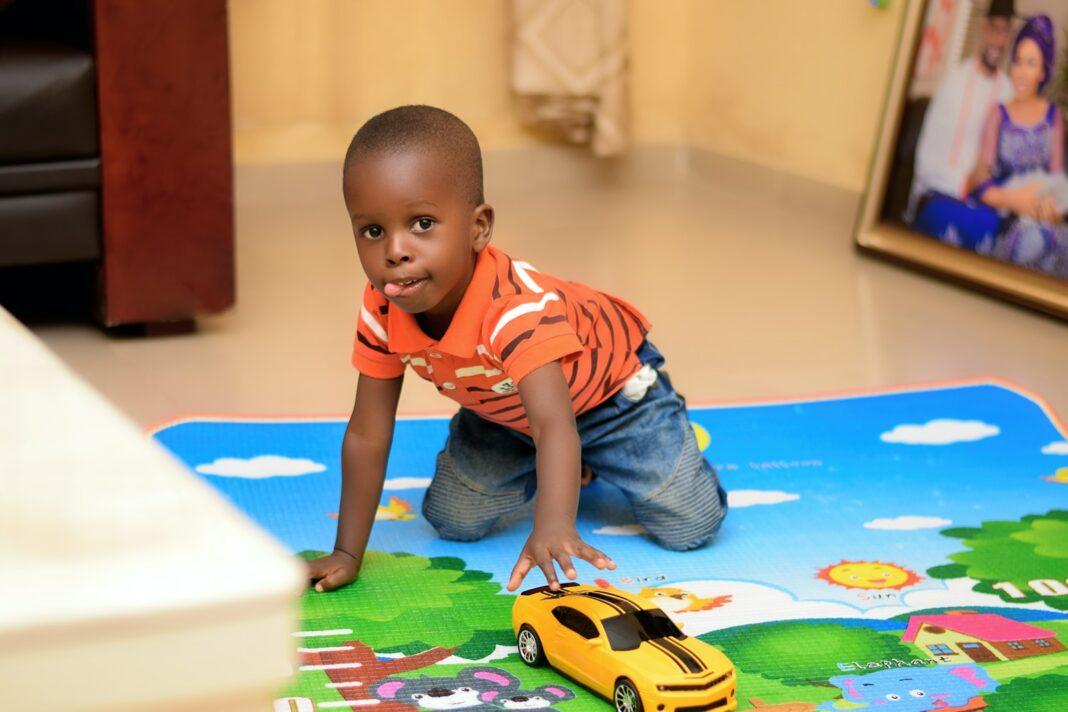 boy playing chevrolet camaro toy on floor