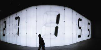 photo of man walking near LED signage